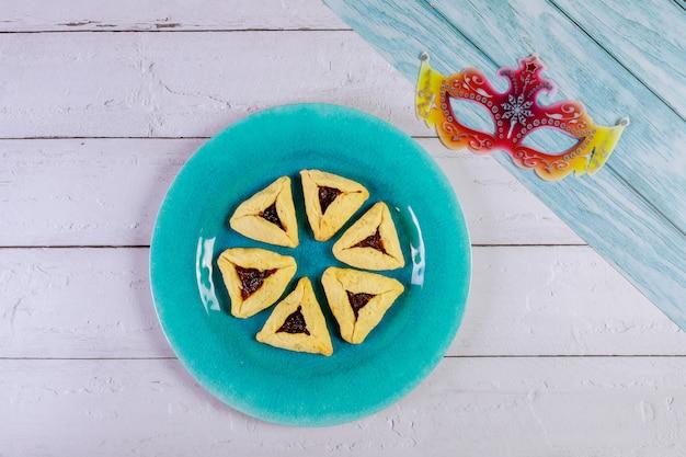Purim met masker en driehoekige koekjes.