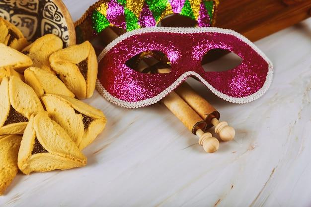 Purim traditioneel met hamantaschenkoekjes, noisemaker en carnaval-masker op houten achtergrond