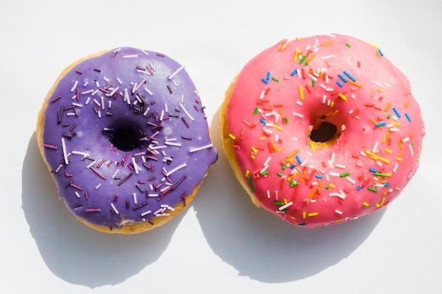 Purpere en roze donuts op witte achtergrond