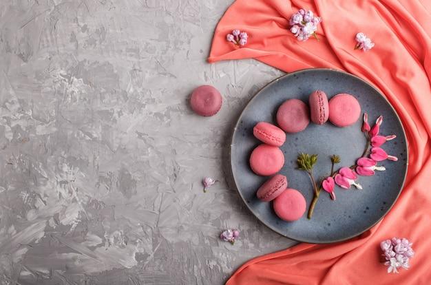 Purpere en roze macaron of makaroncakes op blauwe ceramische plaat met rode textiel