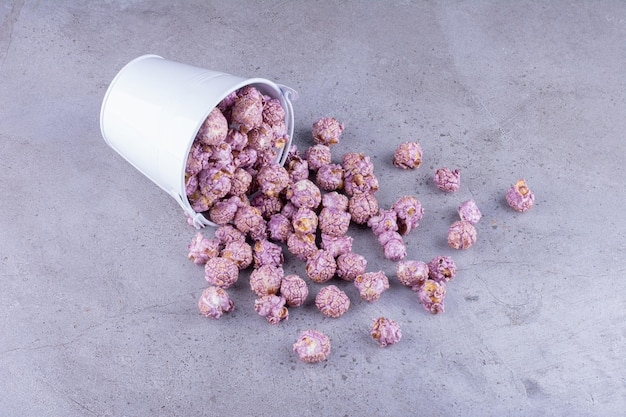 Purpere gekonfijte popcorn die uit een emmer op marmeren achtergrond stroomt. hoge kwaliteit foto