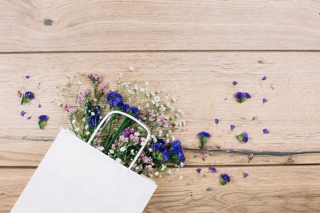 Purpere limonium en gypsophila bloeit binnen de witte het winkelen zak op houten bureau