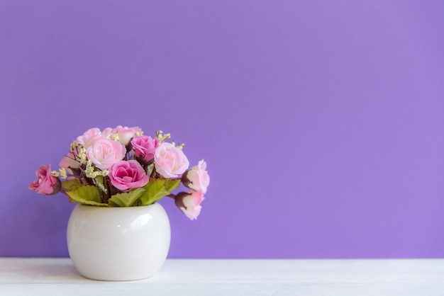 Purpere muur met bloemen op planken wit hout, exemplaarruimte voor tekst. stilleven concept