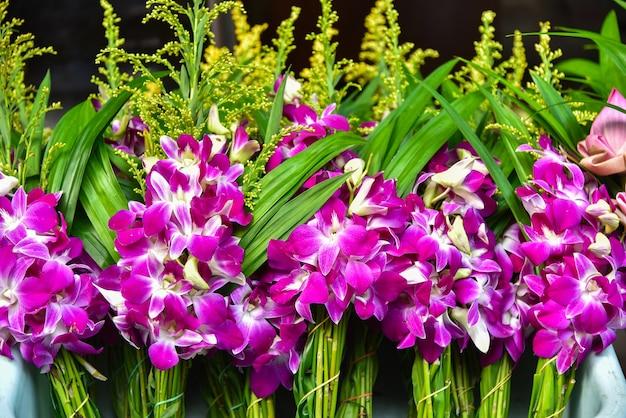 Purpere orchideebloemen bij een thaise tempel
