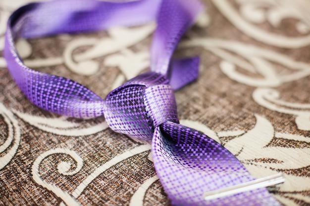 Purpere stropdas met de knoop van de drievuldigheidsband op een bank, close-up