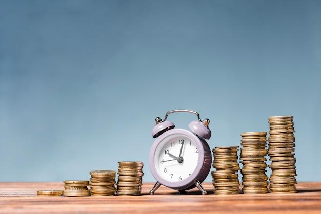 Purpere wekker tussen de stapel toenemende muntstukken op houten bureau tegen blauwe achtergrond