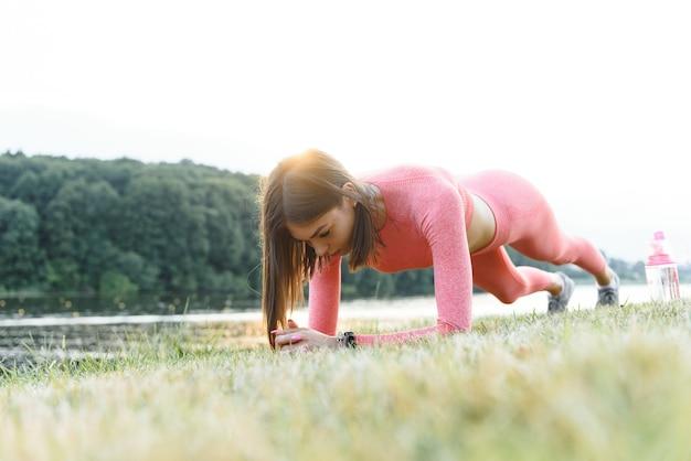Push-ups of push-ups oefenen door jonge vrouw. meisje trainen op gras crossfit krachttraining in de gloed van de ochtendzon tegen een witte lucht met copyspace. gemengd ras aziatisch kaukasisch model.