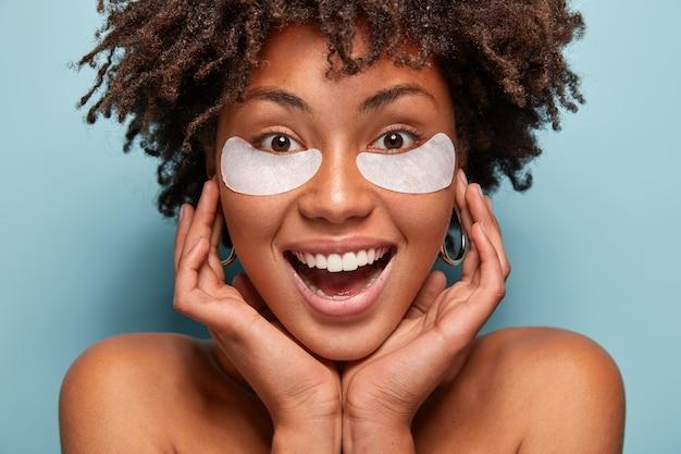 Puur mooie vrouw zorgt voor de huid, heeft onderooglapjes, houdt de handen op het gezicht, lacht breed, heeft witte tanden, afro-kapsel, modellen over blauwe muur. schoonheid en cosmetologie concept