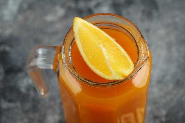 Puur vruchtensap met sinaasappelschijfje op marmeren tafel.
