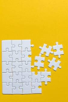 Puzzels geplaatst op een gele achtergrond creatief concept met kopie ruimte