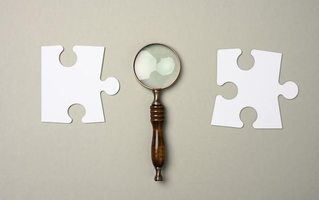 Puzzels rond een vergrootglas op een grijze achtergrond. concept van het zoeken naar getalenteerde mensen, het werven van personeel, het vinden van een oplossing voor het probleem