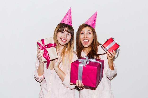Pyjama's verjaardagsfeestje. vrienden die plezier hebben en geschenkdozen houden. verrassingsgezicht, opgewonden emoties. meisjes dragen prop feestmutsen.