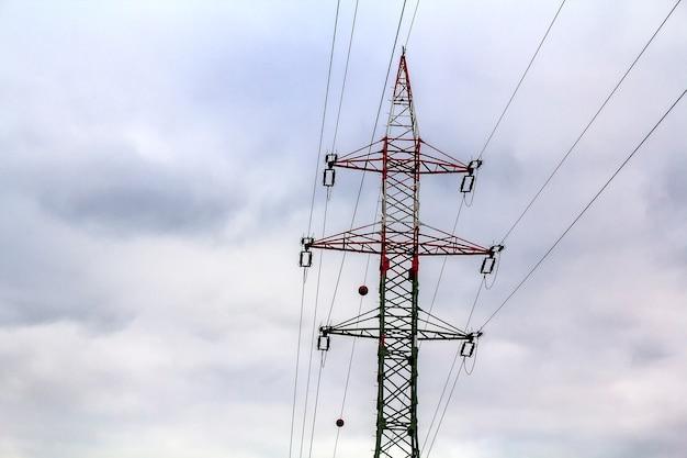 Pylonen en hoogspanningslijnen met levendige lucht, wolken en zon.
