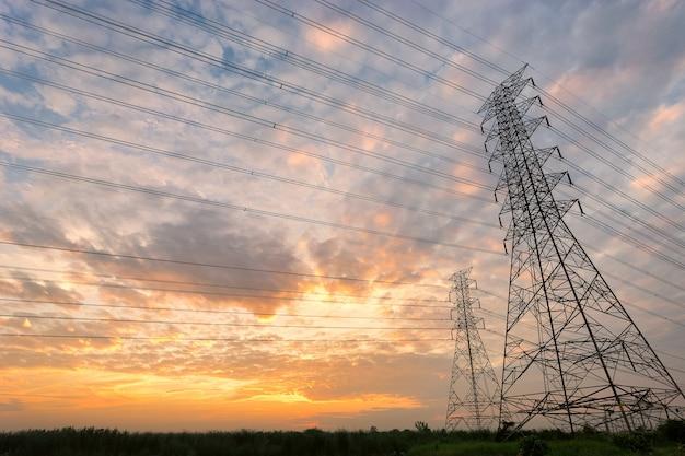 Pyloon en hoogspanningsleidingen die tegen zonsondergang zijn ontsproten