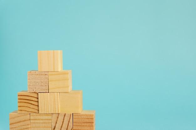 Pyremid constructie gemaakt van houten kubussen op blauwe achtergrond met kopie ruimte. mockupsamenstelling voor ontwerp