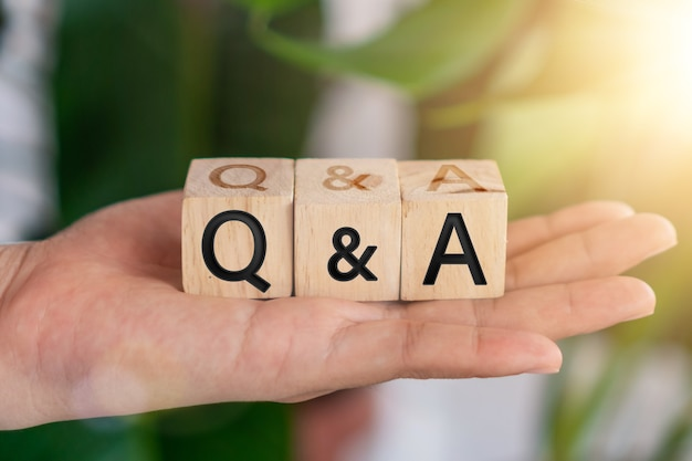 Q en a alfabet op houten kubus in de hand. vraag en antwoord betekenis concept.
