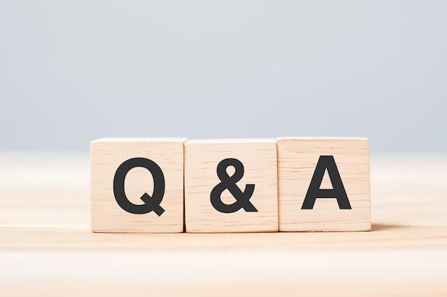 Q en a woord met houten kubusblok. veelgestelde vragen (frequentie gestelde vragen), antwoord, vraag stellen, informatie, communicatie en brainstormconcepten