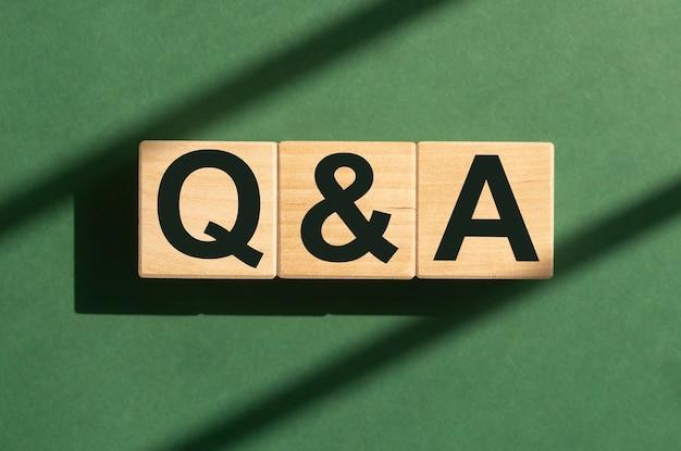 Q en een acroniem qna-inscriptie op kubusblokken op groen eco q-concept
