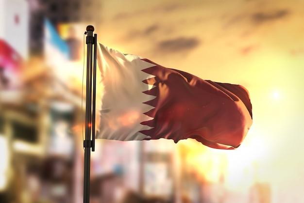 Qatar vlag tegen stad wazige achtergrond bij zonsopgang backlight