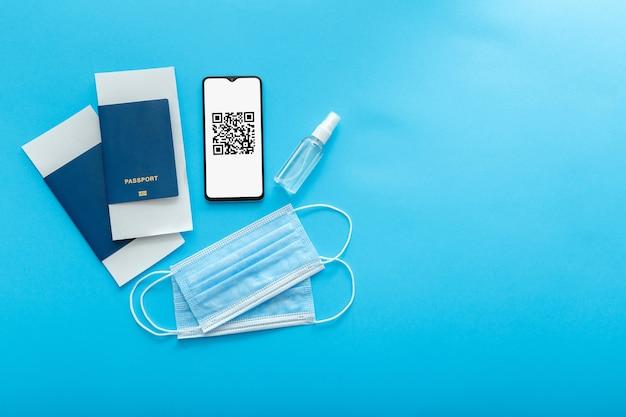 Qr-code pcr-testresultaten, covid-testvaccinatiestempel op smartphonescherm in app. green pass-coronaviruscertificaat voor vliegreizen met een vliegtuig. elektronisch immuniteitspaspoort maskeert tickets blauw plat gelegd