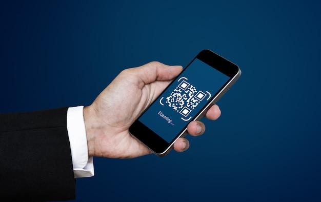 Qr-code scannen betaling en verificatie. zakenman die qr-code van het mobiele telefoonaftasten houden