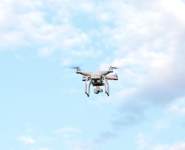 Quadcopter drone met de camera tegen de blauwe hemel