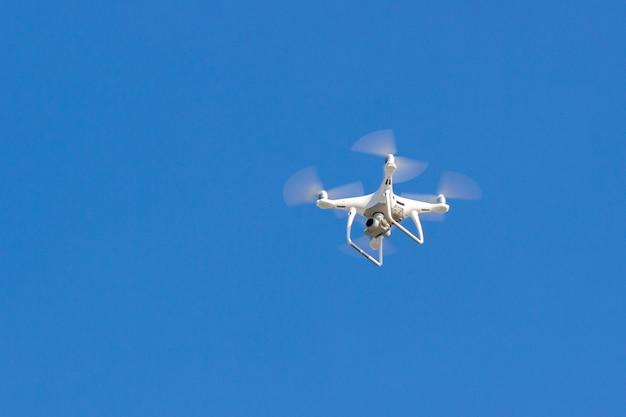 Quadcopter drone vliegt in de blauwe lucht. onbemand luchtvoertuig. video-opnamen op afstand vanaf een hoogte. moderne digitale camera
