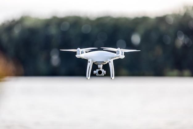 Quadcopterhommel die met een camera over een meer vliegt.