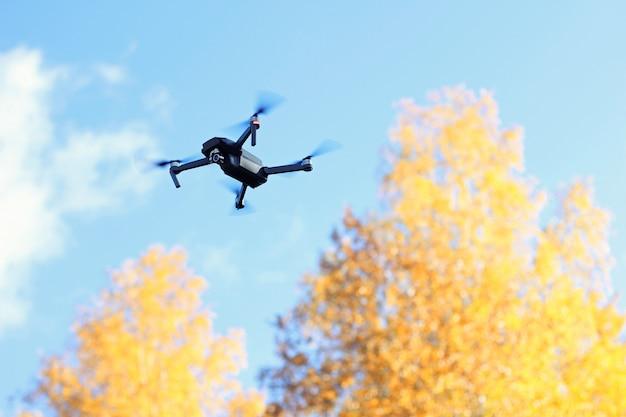 Quadrocopter die naast de de herfstbomen tegen de blauwe hemel vliegt.
