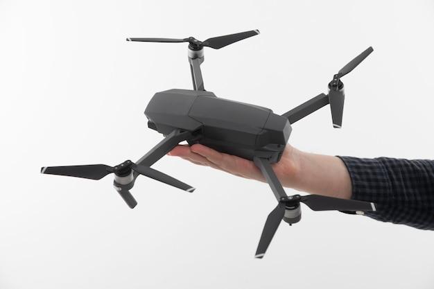 Quadrocopter op de palm van een man op een wit
