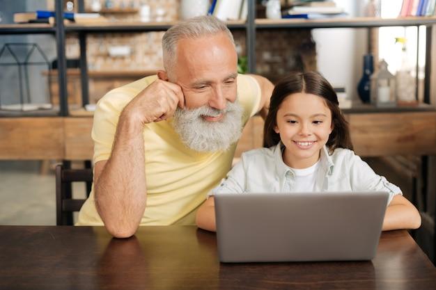 Quality time. aangename oudere man en zittend aan tafel naast zijn kleindochter en samen met haar kijken naar haar favoriete tekenfilms