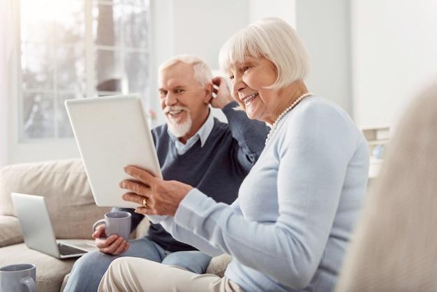 Quality time samen. vrolijke oudere man en vrouw zitten in de woonkamer en kijken samen naar een video op tablet terwijl ze breed glimlachen