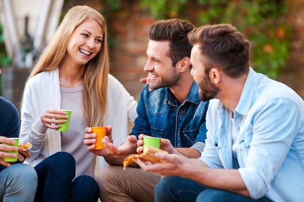 Qualitytime met beste vrienden. groep gelukkige jonge mensen die met elkaar praten en pizza eten terwijl ze buiten zitten
