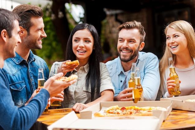 Qualitytime met vrienden. groep gelukkige jonge mensen die pizza eten en bier drinken terwijl ze buiten staan