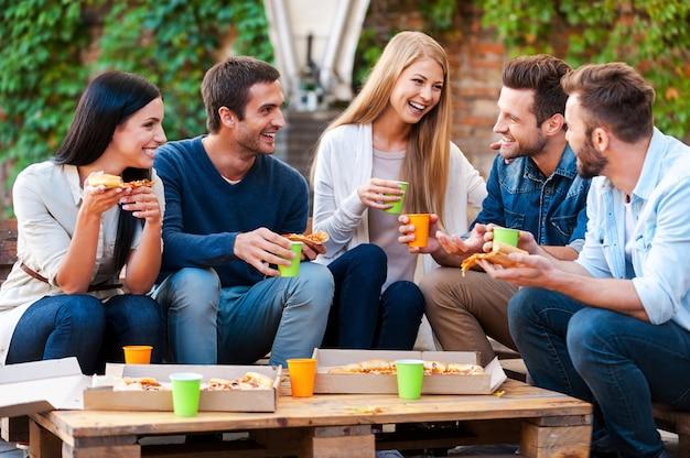 Qualitytime met vrienden. groep vrolijke jonge mensen die met elkaar praten en pizza eten terwijl ze buiten zitten