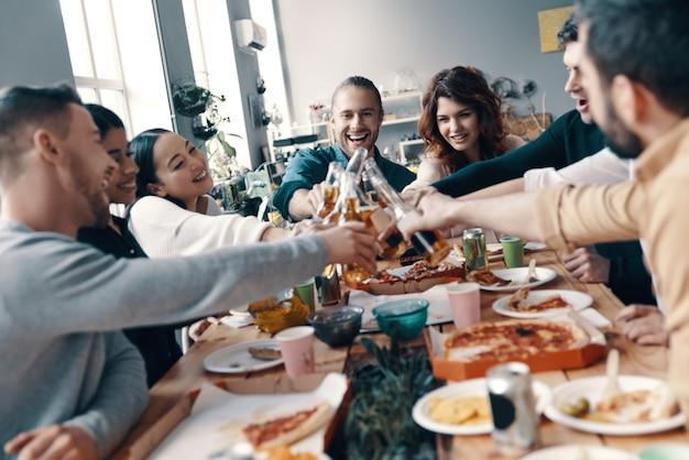 Qualitytime onder vrienden. groep jongeren in vrijetijdskleding die elkaar roosteren en glimlachen terwijl ze binnen een etentje hebben