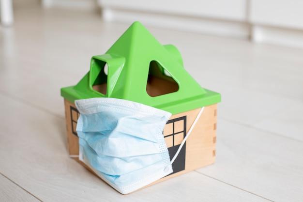 Quarantaine coronovirus concept een speelgoedhuis in een medisch masker staat op de vloer van het huis