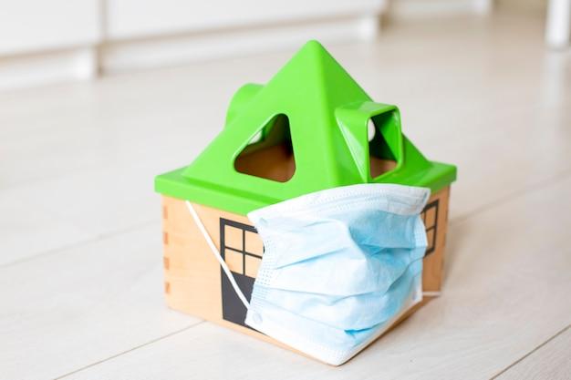 Quarantaine coronovirus concept. een speelgoedhuis met een medisch masker staat op de vloer van het huis.
