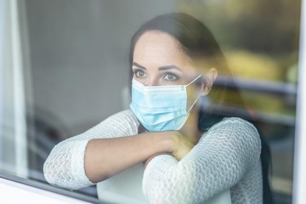 Quarantainemaatregelen van een vrouw met milde symptomen, die zelfs geïsoleerd een gezichtsmasker draagt.