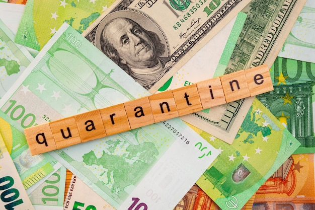 Quarantine-inscriptie op houten kubussen op de textuur van amerikaanse dollars en eurobankbiljetten