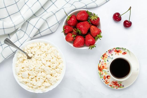 Quark, een kopje zwarte koffie en aardbei op een witte tafel. warme ochtenddrank.