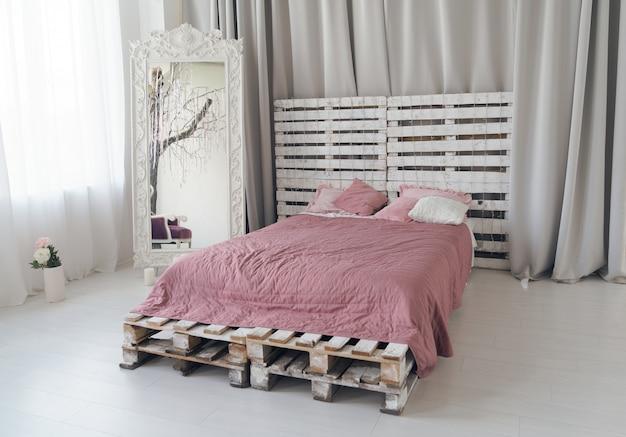 Queen size bed gemaakt van houten pallets en grote houten spiegel in lichte slaapkamer