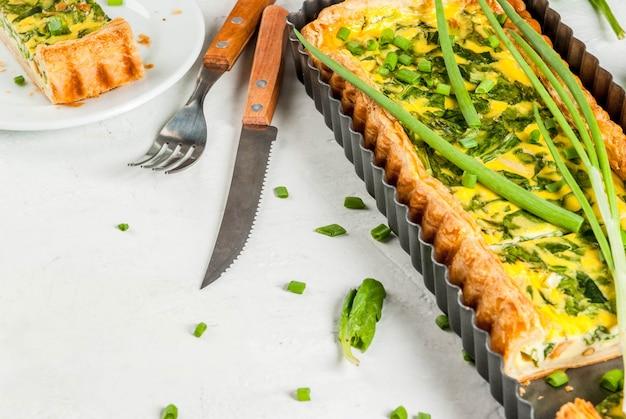 Quiche lorraine van bladerdeeg, met jonge groene uien en spinazie op witte betonnen tafel