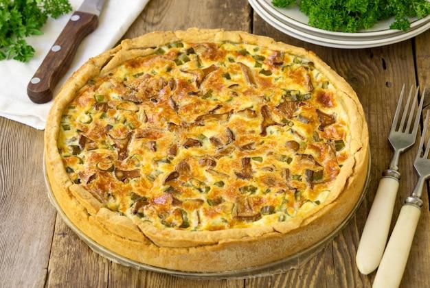 Quiche met cantharellen, kruiden en kaas op een houten achtergrond