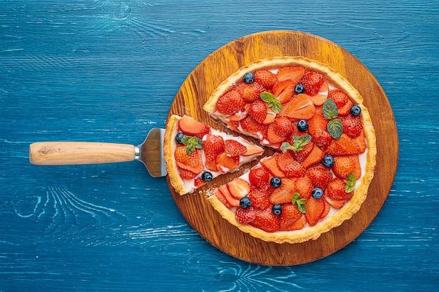 Quiche met limoenschil en aardbeien plakjes met bosbessen en verse muntblaadjes op een blauwe houten tafel. één plak wordt uit de taart gesneden en is klaar om te serveren.