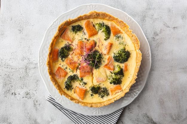 Quiche taart, bovenaanzicht. uitzicht van boven. klassieke quiche van zalm en broccoli gemaakt van korstdeeg met broccoliroosjes en gerookte zalm in een romig scharrelkoekje met vrije uitloop op tafel.