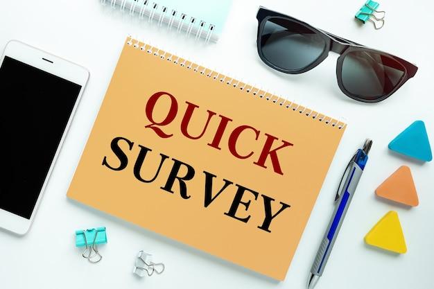 Quick survey wordt geschreven op een notitieblok op een bureau met kantoorbenodigdheden