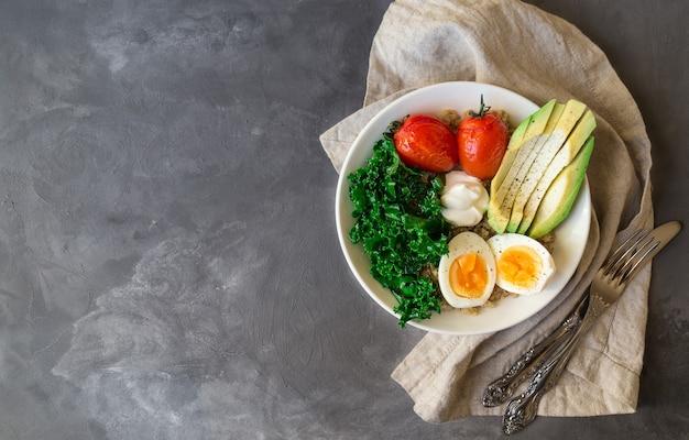 Quinoa buddha bowl met gebakken tomaten, avocado, boerenkool, gekookte eieren en griekse yoghurt op grijs beton
