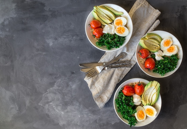 Quinoa buddha bowls met gebakken tomaten, avocado, boerenkool, gekookte eieren en griekse yoghurt op grijs beton