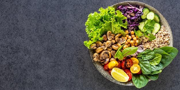 Quinoa, champignons, sla, rode kool, spinazie, komkommers, tomaten, een kom van boeddha op donker, bovenaanzicht.